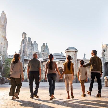 A family walks into Star Wars Galaxys Edge on Planet Batuu, at the Disneyland Resort.