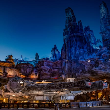 Lights glow on the Millennium Falcon under the towering spires of Batuu as night falls on Star Wars: Galaxy's Edge