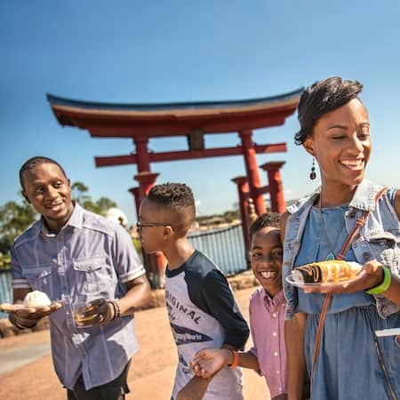 Two young boys walk alongside their parents who are carrying small bites and beverages as they pass a replica of the Itsukushima Shrine Torii Gate in the Japan Pavilion