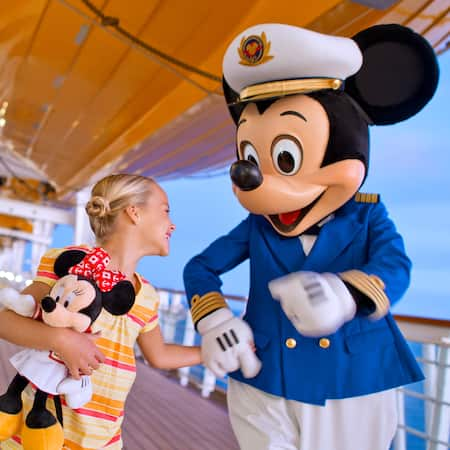 A young girl on a ship deck smiles while holding Mickey Mouse's hand and carrying a Minnie Mouse plush