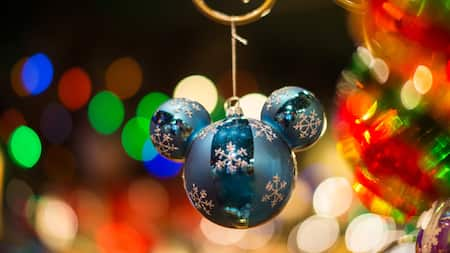 A Mickey Mouse Icon ornament is decorated with snowflakes