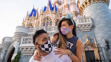 Couple with face coverings look at each other in front of Cinderella castle.