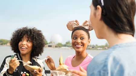 Three females try snacks in Epcot's World Showcase with Spaceship Earth in the distance.