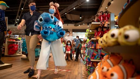 A woman carrying a giant plush Stitch while walking with a man in a store filled with Disney merchandise