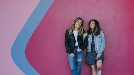 2 young women smile while standing against a wall