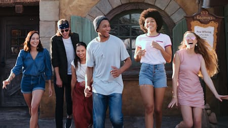 A group of 6 young adults laugh while walking through Magic Kingdom park