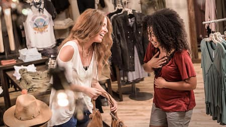 Two female friends laugh and smile as they shop inside Free People, a clothing and accessories boutique at Disney Springs