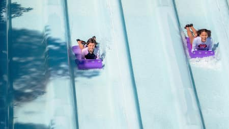 Two children, lying on toboggan-like mats, glide down waterslides at Toboggan Racers.
