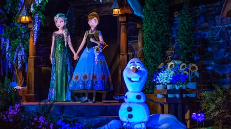 Anna, Elsa and Olaf stand in the Frozen Ever After attraction