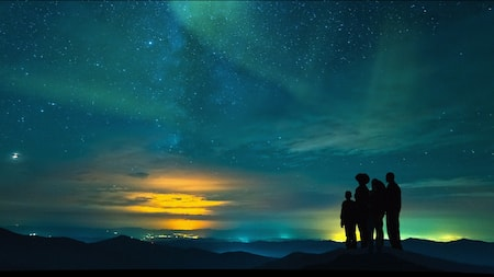 Family stands on a mountain looking at a beautiful blue and yellow night sky