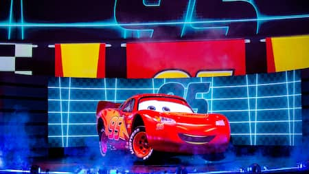 Lightning McQueen, onstage in front of a large crowd, with his racing number featured above him