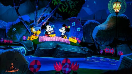 Mickey, Minnie and Pluto enjoying a picnic beside a river at night