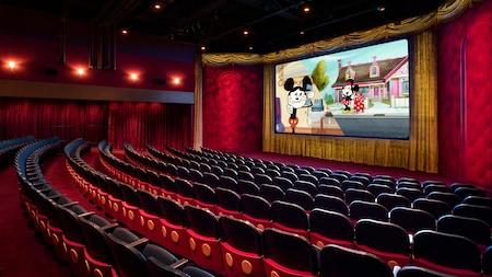 Una sala de cine vacía en la que se proyecta en pantalla una película de Mickey y Minnie Mouse