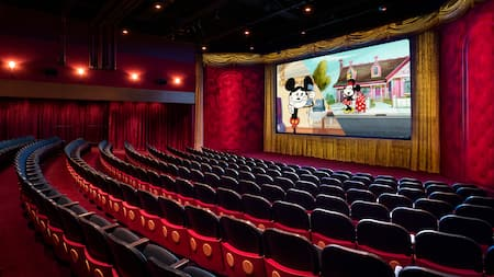 An empty theater with a film featuring Mickey and Minnie Mouse projected on the movie screen