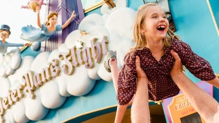 Uma alegre Visitante levantada no ar como se estivesse voando em frente à Peter Pan's Flight