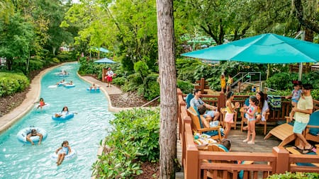 A family sits on a patio with umbrellas while others float down a lazy man river