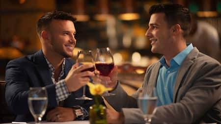 Two men smile at each other from across a table and hold up glasses of red wine