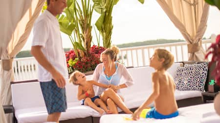 A couple and their 2 sons rest under a cabana with water in the background