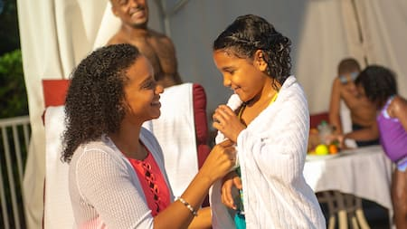 A woman wraps her daughter in a towel in front of a cabana
