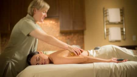 A woman lays face down on a massage table as a masseuse rubs her back