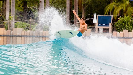 A man surfs a wave with palm trees in the background