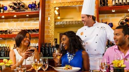 A chef laughing with Guests as they raise their glasses of wine