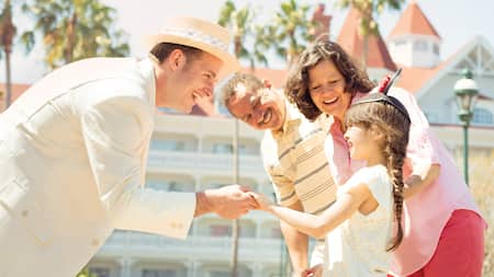 A Cast Member in a boater straw hat greeting a small child and her parents