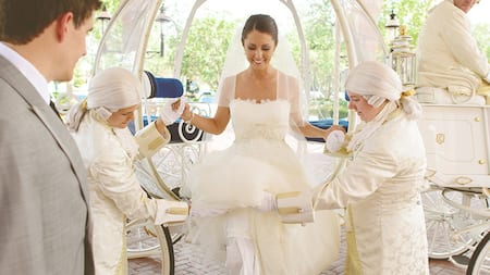 A bride smiles while 2 wigged footmen assist her out of a Cinderella carriage