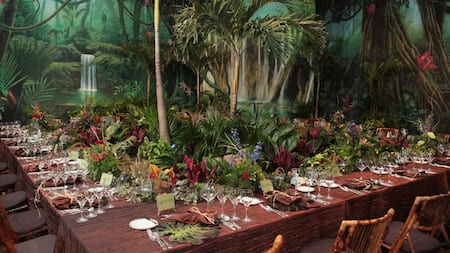 A table set for a large dinner party in an indoor venue decorated like a lush tropical rainforest