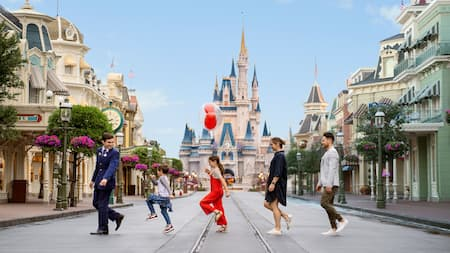 A young family of 4 playing follow the leader with a Disney Cast Member near Cinderella Castle on Main Street