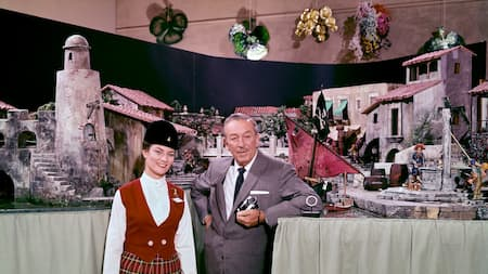 A vintage image of Walt Disney and a Disney tour guide surrounded by small scale models of Disneyland attractions