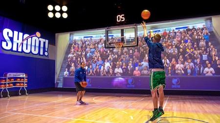 Uma arquibancada virtual e um funcionário da NBA Experience assistem a um Visitante mirando uma bola de basquete em uma cesta em um ambiente de quadra de basquete