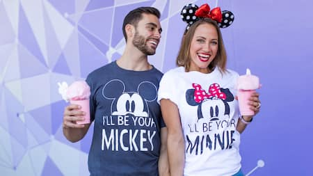 A happy couple wearing his-and-hers Mickey and Minnie t-shirts smile while posing with a frozen treat