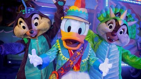 Chip e Dale com trajes de dinossauro ao lado do Donald Duck com trajes de safári
