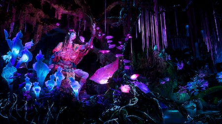 The Na'vi Shaman of Songs in a bioluminescent rainforest on the Na'vi River Journey attraction