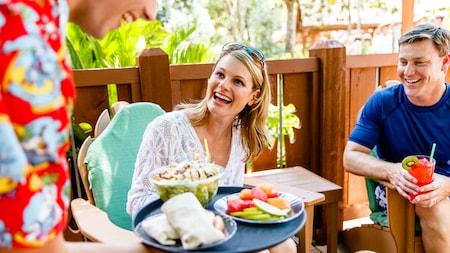 Um casal relaxando ao ar livre desfruta do atendimento de um garçom com pratos em uma bandeja
