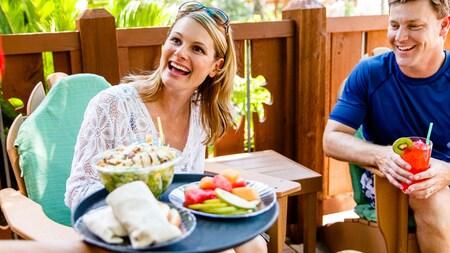 Una pareja al aire libre, disfrutando mientras un mesero llega con comida en una bandeja