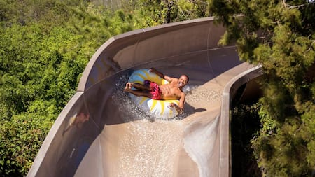 A man slides down Runoff Rapids on an inner tube