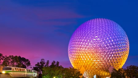 A monorail glides by Spaceship Earth at sunset