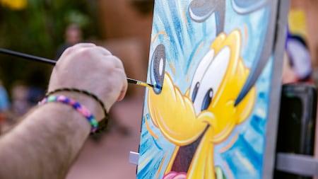 Um artista pinta o Pluto em uma tela