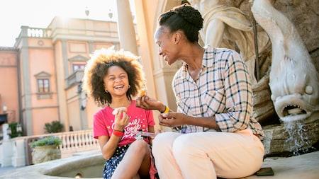 Una mujer y su hija sentadas al borde de una fuente comparten un snack