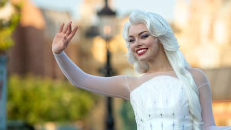 Queen Elsa smiling and waving at Epcot