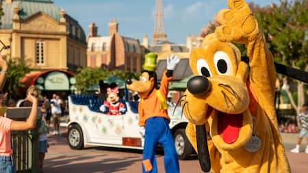 Goofy and Pluto waving to Guests in the France Pavilion, while Mickey and Minnie Mouse wave to Guests from a nearby vehicle