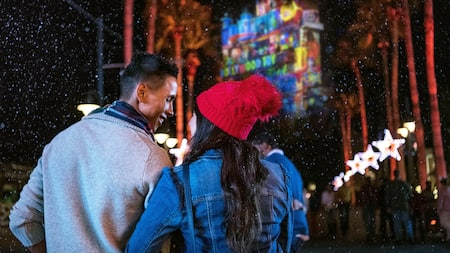 A couple smiles at each other as snow falls on Hollywood Boulevard in Disney's Hollywood Studios