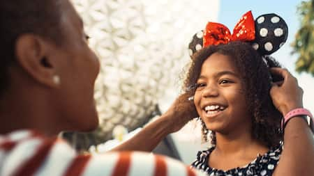 A mother putting Minnie Mouse ears on her daughter in front of Mission Space in Epcot