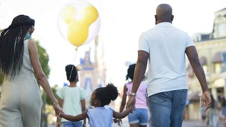 A mom, dad and their 3 kids walk down Main Street U S A, wearing face masks and holding a Mickey balloon