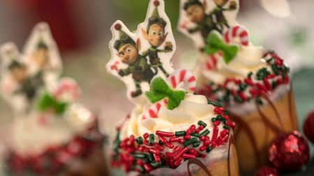 Vanilla cupcakes topped with cutouts of elves from Prep & Landing