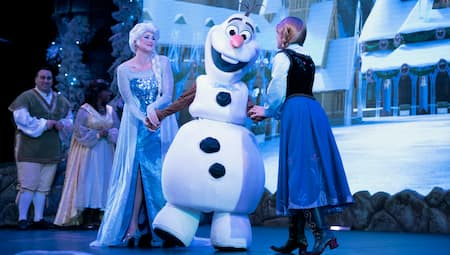 Elsa, Anna and Olaf sing on stage