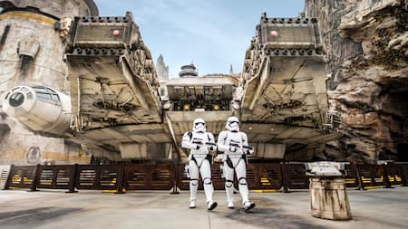 Two Stormtroopers march in front of the Millennium Falcon docked in Batuu