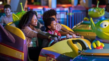 A woman and 2 young boys smile while riding Alien Swirling Saucers